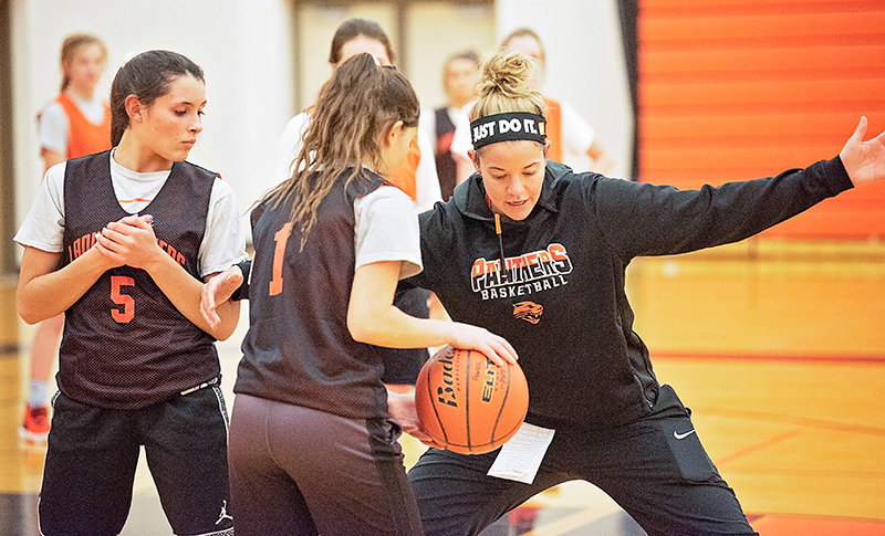 Panther girls' basketball coach Chelsea Buher works with Powell High School seniors Sabrina Shoopman (left) and Karina Boreen (center) during a Monday practice. Although the squad enters the season with very little varsity experience, Buher thinks her team will defy many people's expectations.