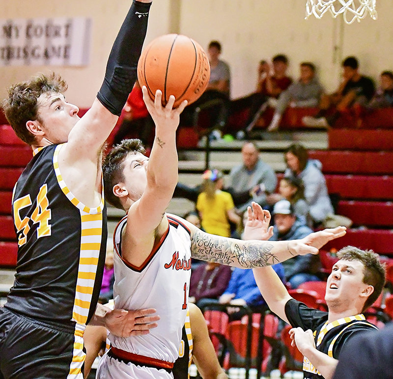 Max Dehon, a 6-foot, 5-inch Trapper, gets his shot despite the defense of 7-foot Jonathan Hall in NWC's impressive conference victory over Eastern Wyoming, 88-65, on Saturday.