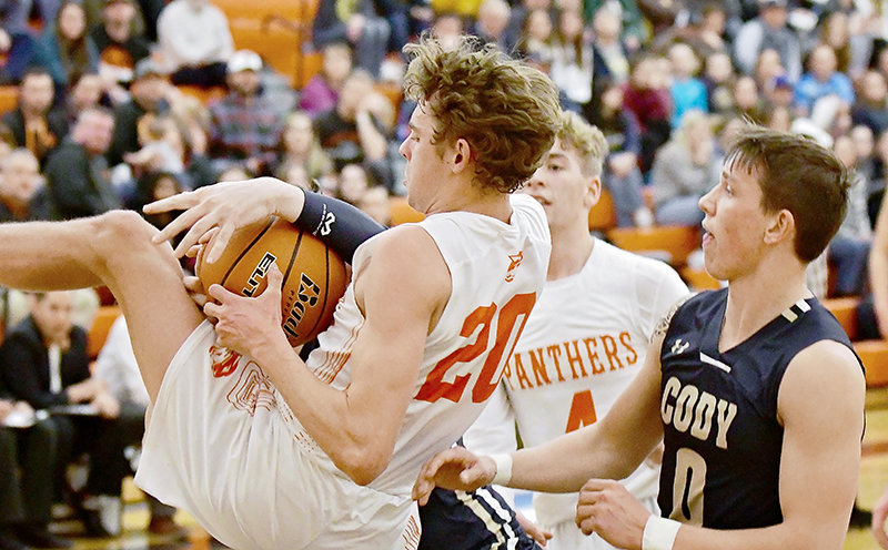 Panther senior Jesse Brown seems to curl his entire body around this high-flying rebound against Cody on Friday night. At right are Bronc Nic Talich and Panther Mason Marchant. Cody held off the rallying Panthers, 56-51.
