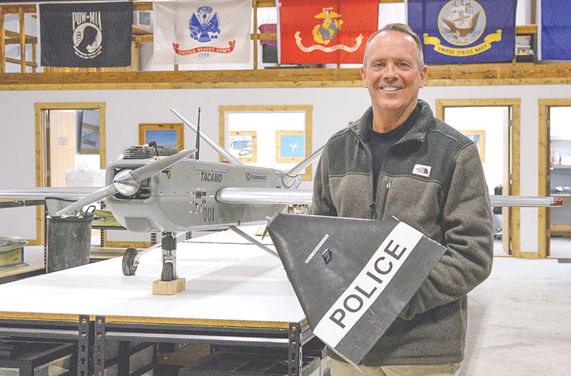 Thomas Rullman, president and CEO of GT Aeronautics, holds a bandito drone inside the company's hangar at the Powell Municipal Airport. In military operations, the banditos can be used against ground or air targets. On the table is Tacamo, which can hold two of the banditos.
