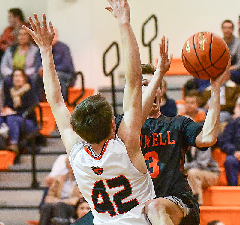 Powell senior Aidan Jacobsen scored on this drive despite the solid defense of Burlington Husky Gideon George (42). Jacobsen contributed five points to his team's 69-50 Tuesday road win.