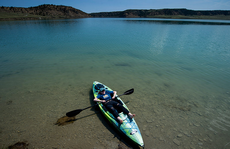 Amanda Marco relaxes, seemingly having the lake to herself, in her kayak while visiting Upper Sunshine Reservoir, near Meeteetse, last May. Rivers, lakes and other outdoor spaces generally remain open in most of Wyoming while neighboring states have instituted shelter-in-place rules and limited access to outdoor recreation.