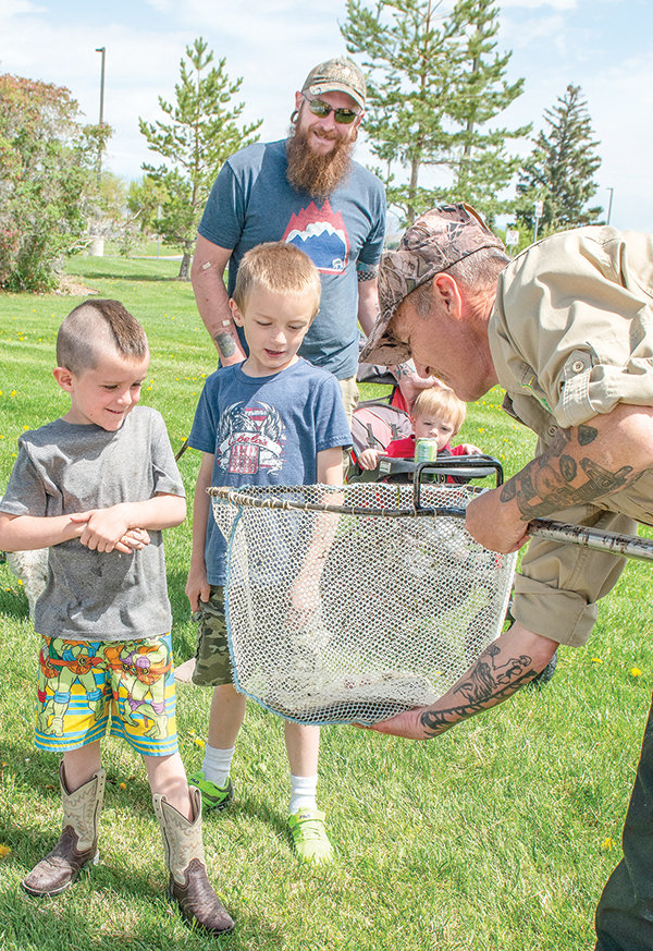Shane Allen, of the Cody Wyoming Trout Ranch, shows off a nice trout to Jason Burns and his children (from left) Robert, Benjamin and AJ, and their pet pooch, Scotty. The company stocked the fishing pond at at Homesteader Park with more than 500 rainbow and brook trout last week.