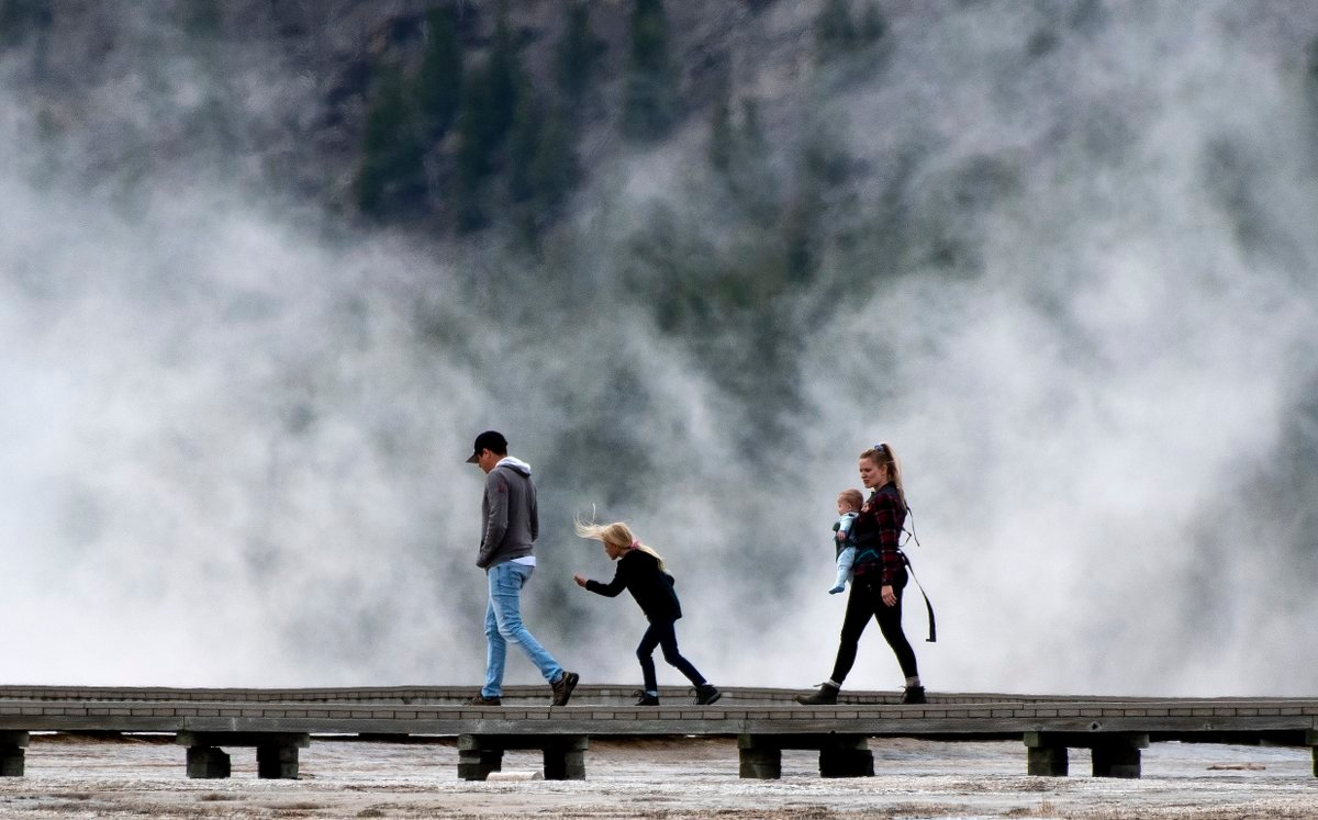 Visitors stroll across a boardwalk in Yellowstone National Park on May 18, the opening day for the park's East and South entrances. On Monday, Yellowstone's other three entrances will open for the summer season.