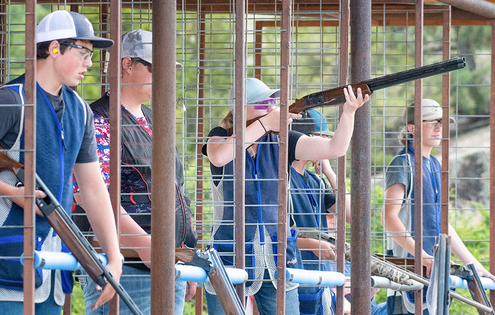 Hannah Sears (center) takes aim during the 5-stand competition at the Cody Shooting Complex last week. The competition involves five stations, or stands, and six to 18 strategically placed clay target throwers (called traps). Competitors shoot in turn at various combinations of clay targets. Sears took third in the event and won four awards overall during the three-day competition.