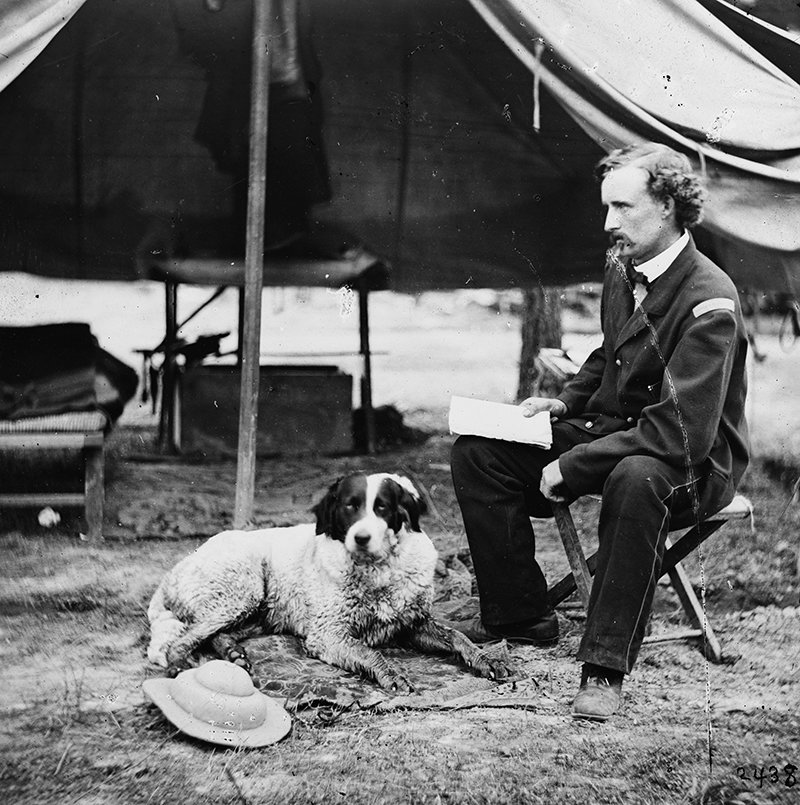 This photograph of George Armstrong Custer was taken during the summer of 1862 in camp. A dog lounges on a rug.