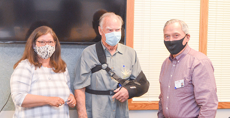 Powell Hospital District trustees Deb Kleinfeldt (left) and R.J. Kost (at right) present Larry Parker with gifts and recognition on Monday, after he announced his retirement from the hospital board following 10 years of service.