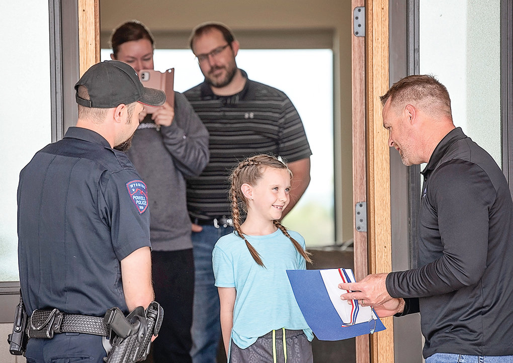 Parkside Elementary School Principal Jason Hillman (right) presents a Citizenship Award to Tenley Shorb at her family's home last month. Her parents, Tara and Danny Shorb, are pictured in the background. At left, Trevor Carpenter, school resource officer for Powell schools, joined Hillman in presenting the awards to Parkside students.