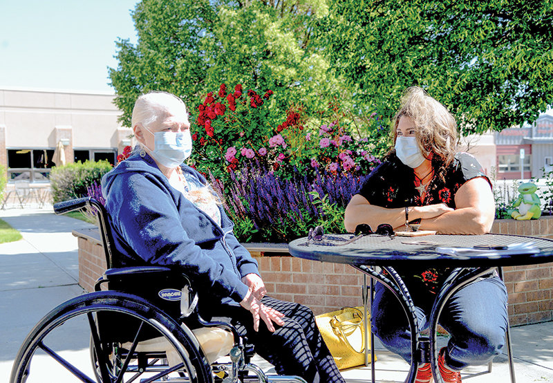 For the first time in three months, Powell Valley Care Center resident Kelly Mikeworth (left) is able to sit at a table with her daughter, Maureen Mikeworth, on June 26. The facility recently began permitting these face-to-face visits.