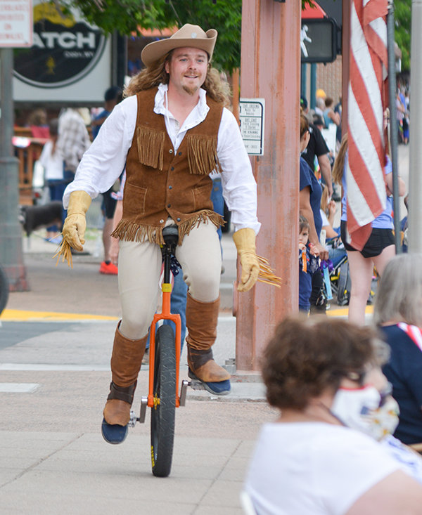 A unicyclist dressed as Buffalo Bill makes his way down a Sheridan Avenue sidewalk during the Stampede parade on Friday. The crowd was small on Friday, but swelled on Saturday to more typical levels.