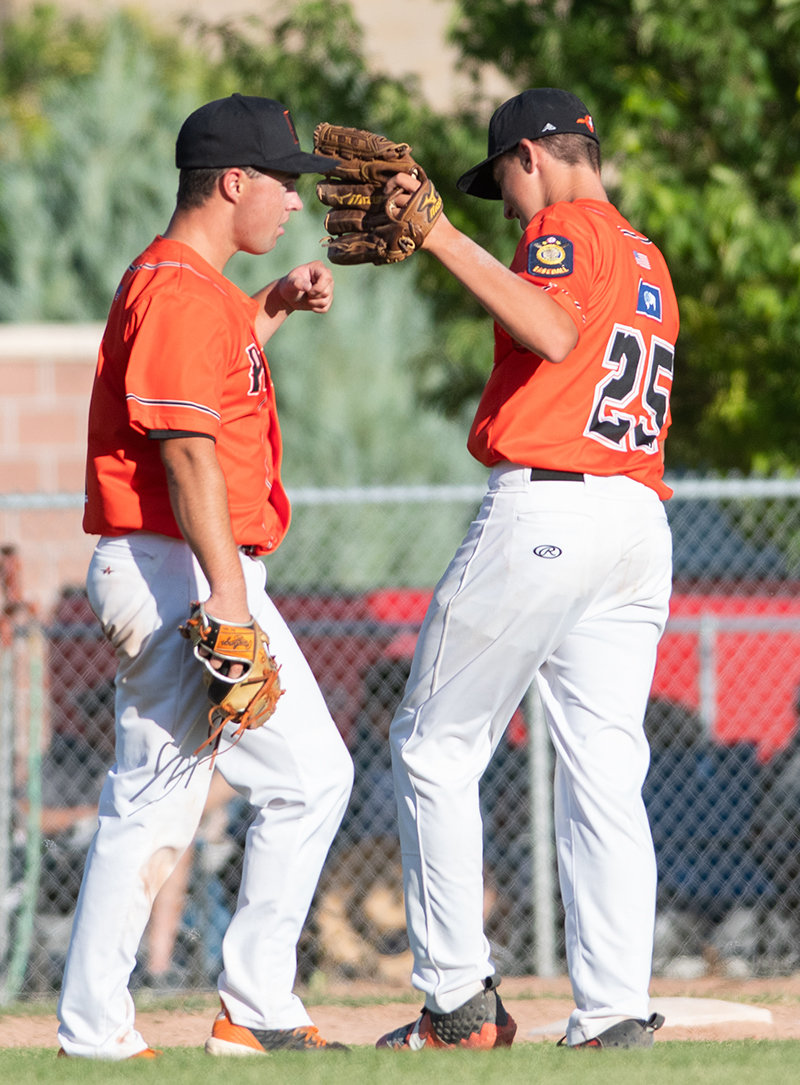 Colin and Cade Queen converse before Colin takes the mound against the Lovell Mustangs last week. This is the first — and final — year the brothers have played together on the Pioneers A team.