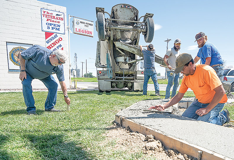 From left, Bud Schrickling of the Hughes-Pittinger American Legion Post 26 removes a stake from the ground while workers Chris Sessions, Dade Greene, Nate Hunt (in front) and Kyle Henke pour and smooth the base for Powell's Wall of Honor in mid-July. It's set to be unveiled on Oct. 14.