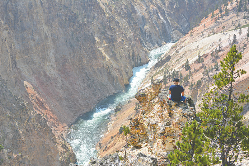An artist perches on a rocky outcrop in the Grand Canyon of the Yellowstone, after illegally going off-trail near Inspiration Point on Aug. 21. Visits to Yellowstone National Park have sunk this year, but it's the reduction in park lodging services that has led to a huge drop in Park County's lodging tax collections.