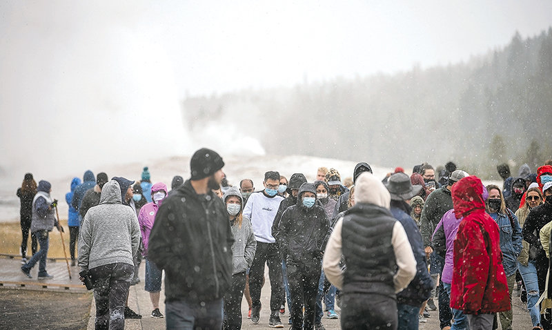 Visitors to Yellowstone National Park's Old Faithful turn to leave before the eruption was finished late afternoon on Monday. Snow and wind dropped temperatures substantially while waiting for the geyser, part of a regionwide cold snap that brought record lows.