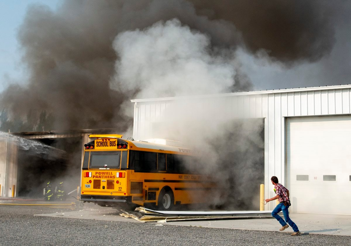 A Powell High School activities bus is driven out of the smoking bus barn on Monday morning. Powell firefighters were able to help save multiple buses and vehicles from the fire through quick action.