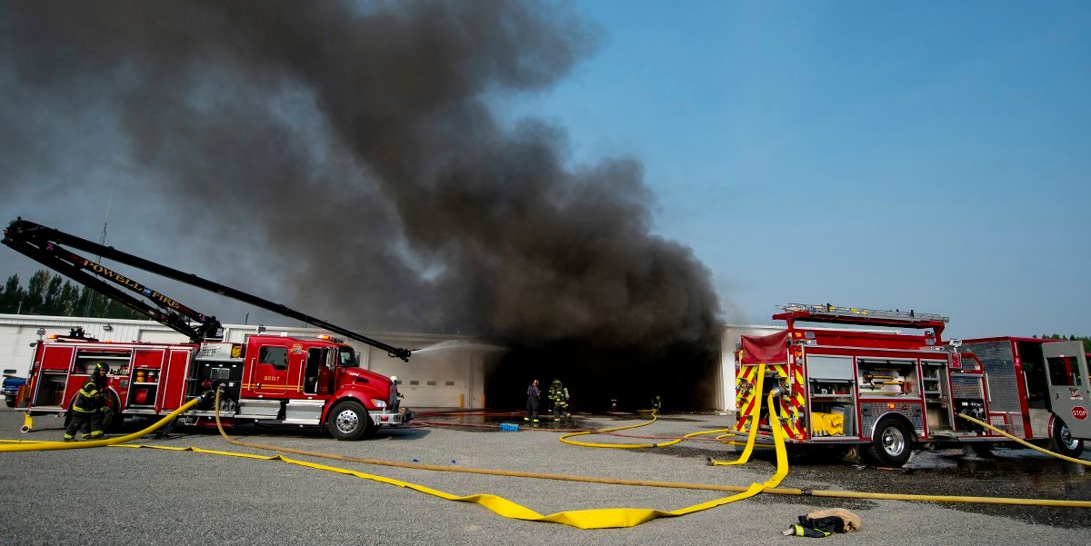 Smoke billows out of the Powell school district's bus barn Monday morning, while firefighters work to put out the fire.