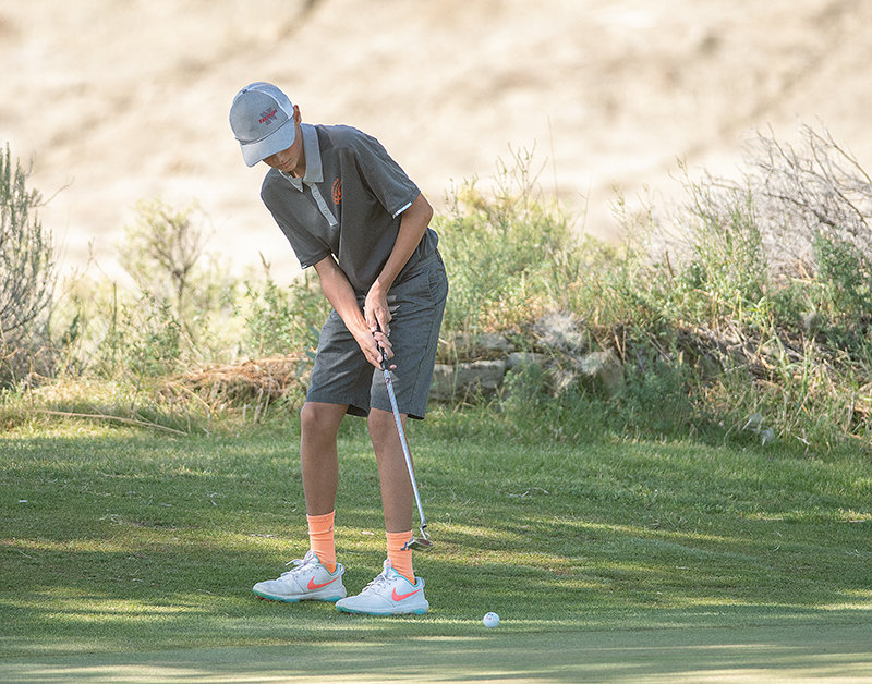 PHS freshman Gunnar Erickson putts from the fringe in the Class 3A West Conference golf tournament at Powell Golf Club on Friday. Erickson shot a 94 in the event, finishing 16th.