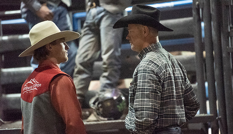 NWC assistant coach Dan Mortensen (right) talks with Austin Herrera after his bull ride last month during the Trapper Stampede Rodeo in Cody. Mortensen is a six-time world champion in saddle bronc, a one-time world champion in all-around and a ProRodeo Hall of Fame member.