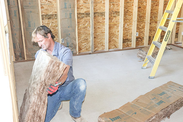 Shane Shoopman, co-owner of Smooth Edge Construction, installs insulation.