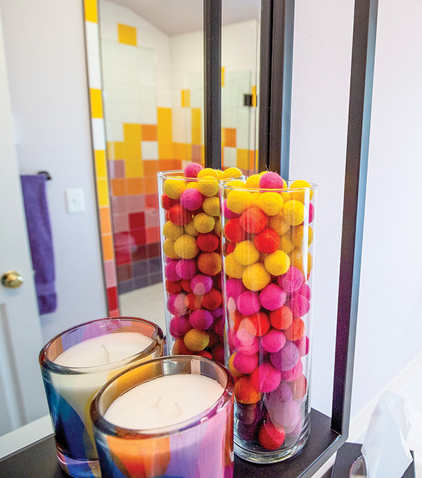 A vase of colorful beads matches the colorful guest bathroom. The new shower can be seen in the mirror.