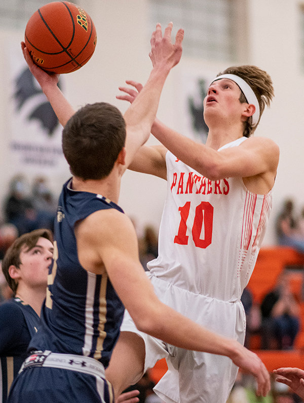 Senior Trevor Groves attempts a layup over Cody's Luke Talich (2) Saturday against Cody. Coach Mike Heny noted the team's increased cohesion in the midst of its three-game winning streak.