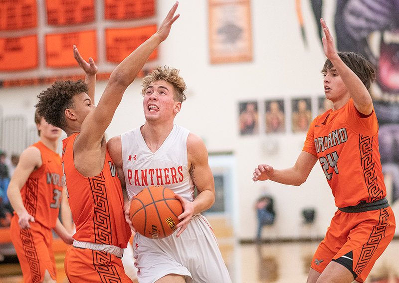 Mason Marchant drives between two defenders Saturday in Powell's 64-53 win against Worland. Marchant led the team with 19 points in the dub.
