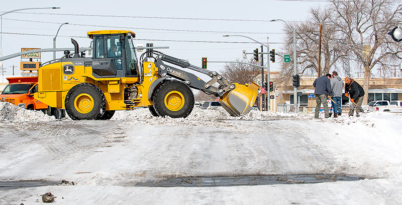 Ray Branstetter, Andy Metzler and Ted Marshall chip away at ice built up on the tracks crossing Bent Street south of Coulter while Bill Gullion runs a front end loader while they work Tuesday to smooth the road.