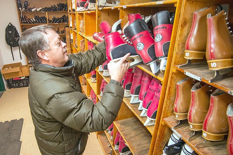 Powell Recreation District Director Colby Stenerson works the rental counter at the warming hut. The district has hundreds of sizes of skates to rent. The rink is open until 10 p.m. daily.