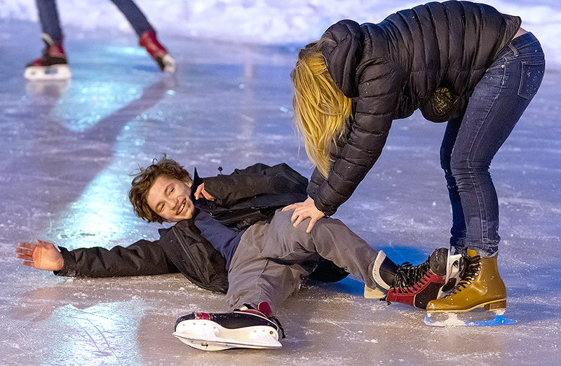 Darren Smith gets help from a friend after falling at Homesteader Park's skating rink Friday night.