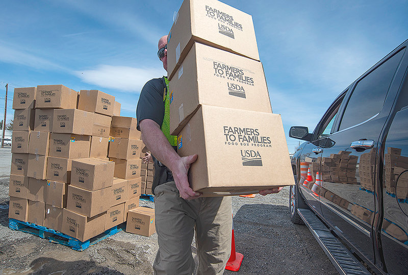 Matthew Smith, a team member with Park County's Community Emergency Response Team, carries donated food Friday to vehicles during a drive-thru free food operation at the Park County Fairgrounds. The Food Bank of the Rockies, assisted by local officials and volunteers, delivered 34,500 pounds of food to needy families in the area.