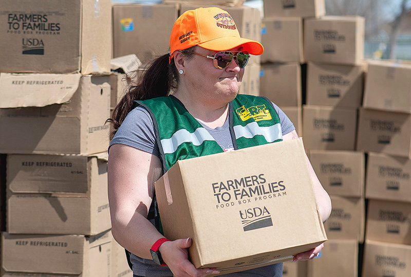 Melinda Humsaker, a CERT team member, helps distribute food to needy families. The boxes included fruits and vegetables, meat and milk.