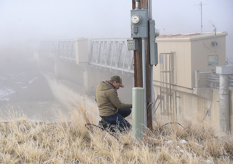 Jason Burckhardt, Wyoming Game and Fish Department fisheries biologist, does some work at a utility pole by Willwood Dam at the start of the operation on a foggy Wednesday morning.