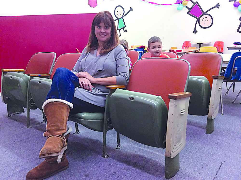 Kerri Meyer sits in the seats of the former auditorium of the old Middletown Area High School, as Connor sits in the second row.
