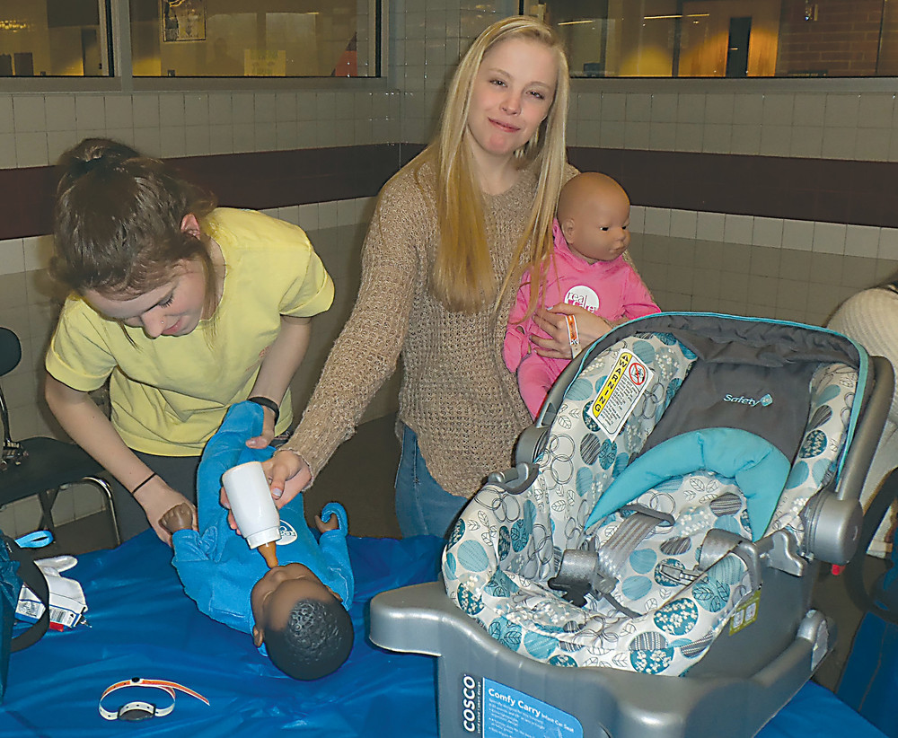 Lower Dauphin High School students Alexis Putt and Taylor Noss tend to a infant simulator that's used for the high school's Child Development classes at the Lower Dauphin Curriculum & Technology Fair on April 1.