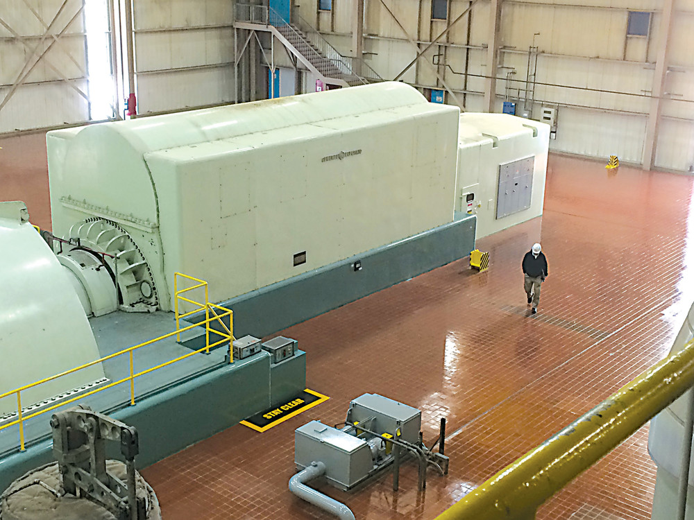 A Three Mile Island employee walks past the generator at the plant in this November 2016 photo.