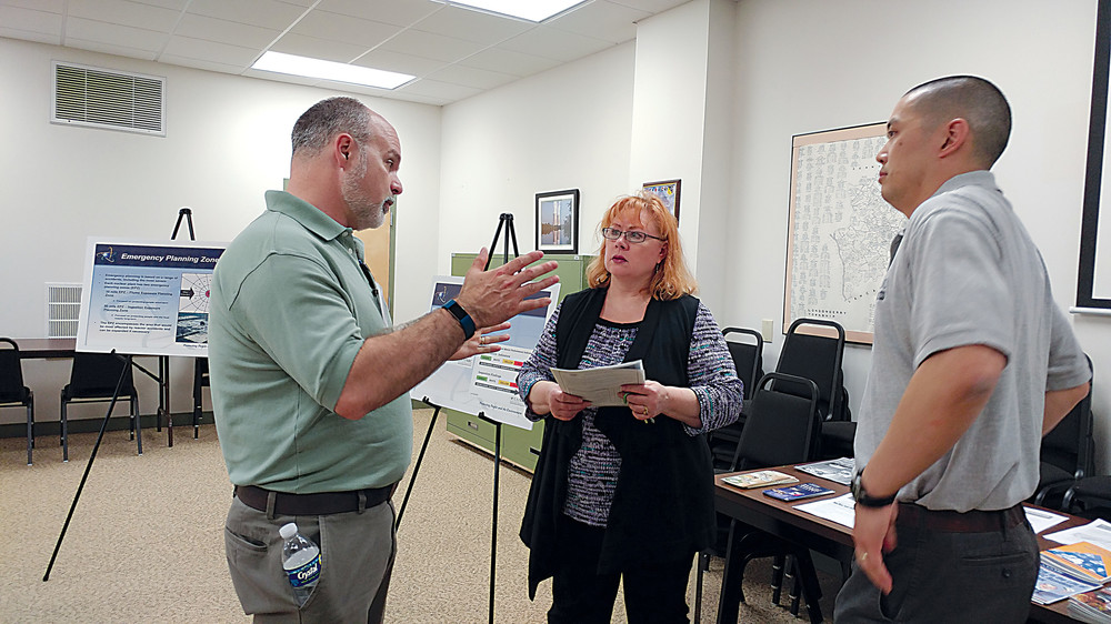Joyce Vigilante talks with David Werkheiser of the Nuclear Regulatory Commission about the NRC's 2016 inspection results at Three Mile Island as Brian Lin of the NRC listens, on Thursday, April 20.