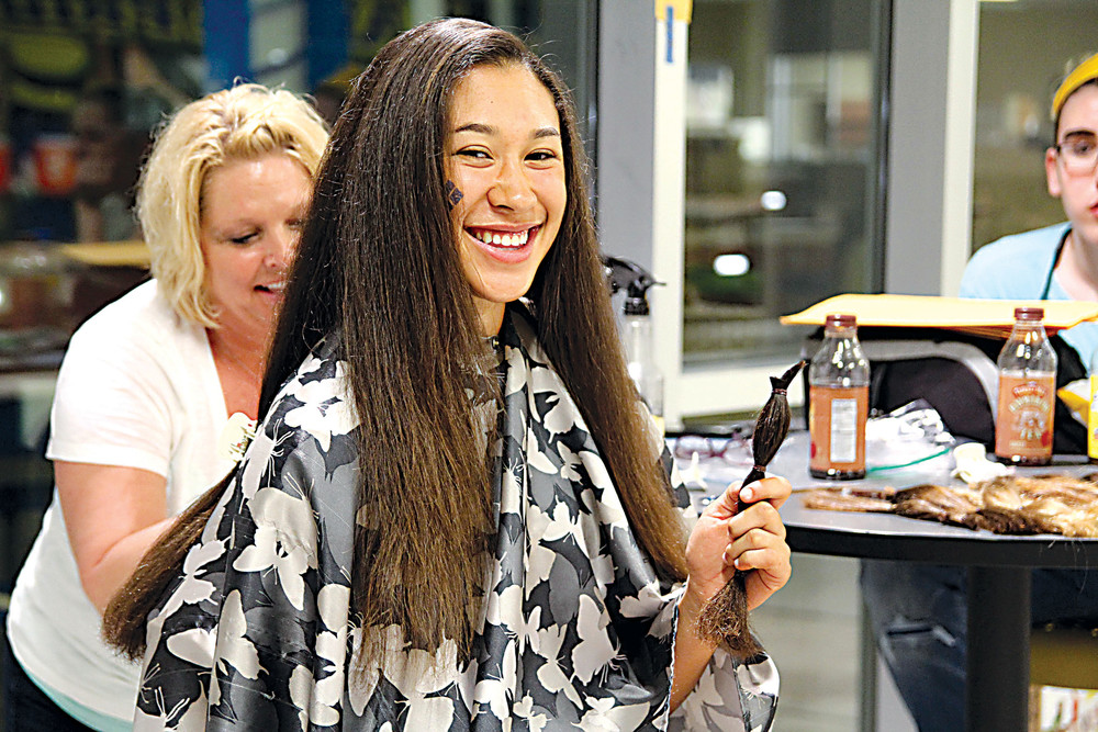 Hayli Akakpo-Martin and 10 other girls got haircuts Friday to help make wigs for cancer patients.