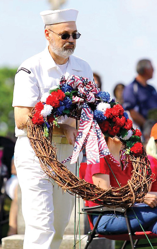 A veteran places a wreath on a grave during the Memorial Day ceremony at the Middletown Cemetery on Monday, May 30, 2016.