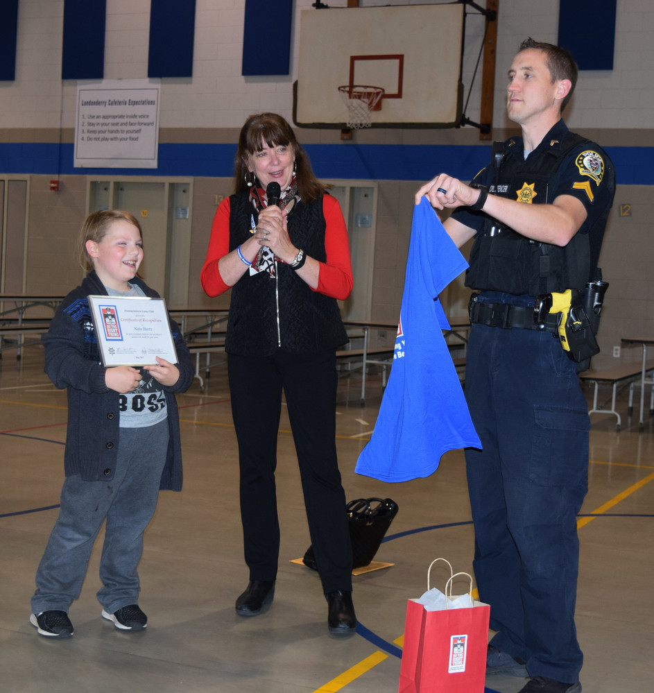 Nate Hartz receives his T-shirt from Communities That Care program director Kathy Peffer and Hummelstown Police Cpl. Eugene Spencer.