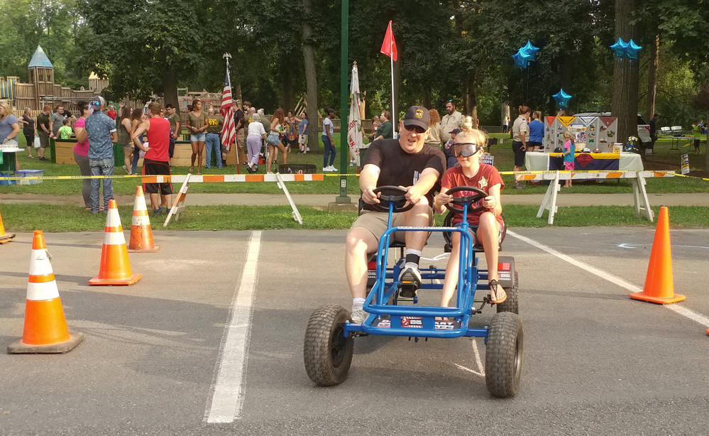 Hope Burger, 10, attempts to navigate an obstacle course while wearing alcohol goggles to simulate the effects of driving while impaired during the 2017 National Night Out at Hoffer Park. Helping to guide her is Middletown patrolman and drug recognition expert Jeffrey Weaver.