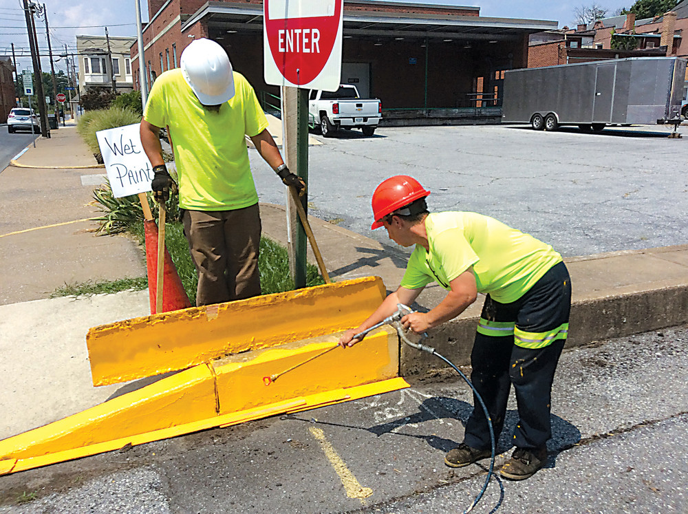 Adam Erdman (standing), a seasonal worker with Middletown Public Works, assists fellow Public Works employee Kari Keller as she applies a fresh coat of yellow paint to the curbing of a street in downtown Middletown.