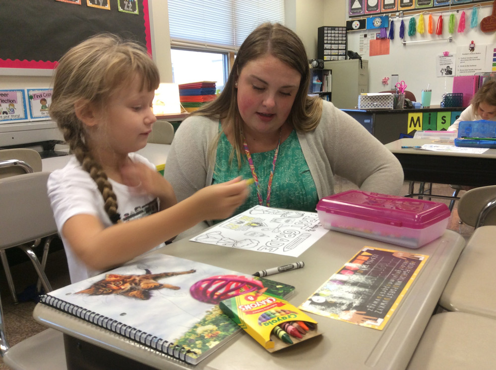 New Kunkel Elementary first grader teacher Janelle Dukes works with student Eden Irvin on the first day of school on Monday, Aug. 28.