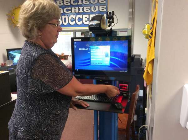School secretary Tina Shope inserts a driver's license into the Scholar Chip Visitor Management System at Kunkel Elementary School on Monday, Aug. 28.