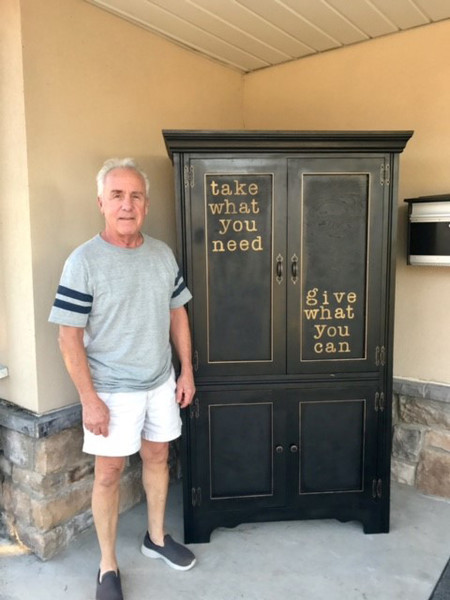 Raul Perez Jr. of Hummelstown stands next to the old dresser he refurbished into Middletown's Little Free Pantry at the entrance to the borough police station on East Emaus Street. The pantry is now open.