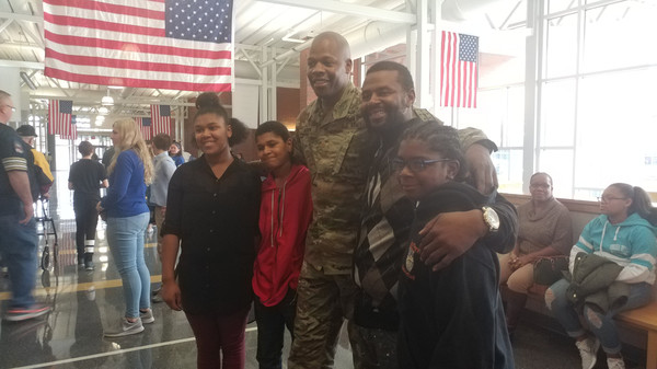 United States Army Maj. Tracy Brown and his family pose for a picture at the conclusion of the middle school ceremony. From left to right are Zhanaza Russell, Basem Russell, Brown, James Russell, and Nasir Russell.