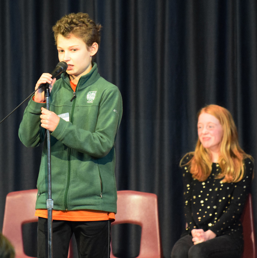 Toby Waters spells a word during the later rounds of the bee while Abigail Foran looks on.