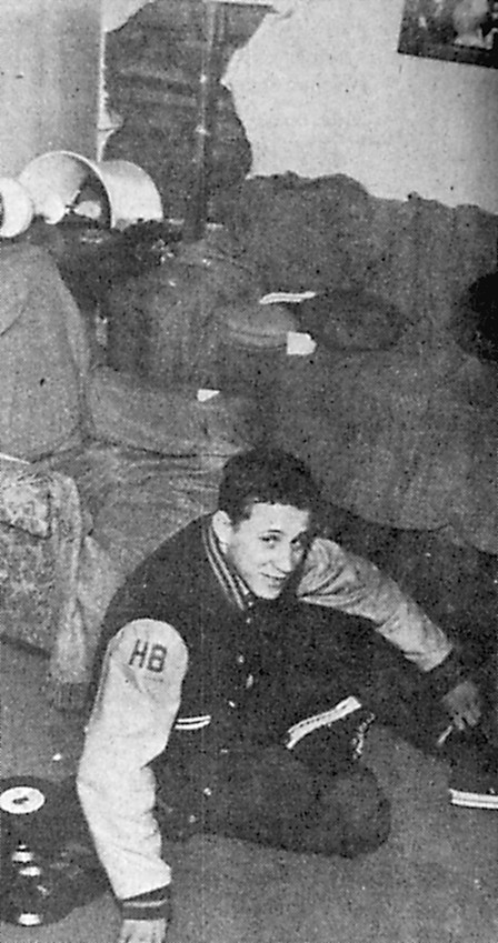 Lou Souders, local Blue Raider athlete, sits on the floor to show a Press & Journal photographer his position when a car crashed into the Stewart home on Valley Lane on Tuesday night. Pictured at rear is damage to the wall and home furnishings. Souders and Betsy Stewart were playing records when the crash came.