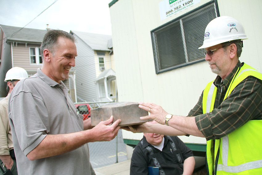 Gary Snyder, construction supervisor for the Felton Lofts project, hands the time capsule to Joe Zimmerman, Steelton-Highspire School District's building and grounds director. The box was removed from the cornerstone of the 100-year-old former Steelton Elementary School.