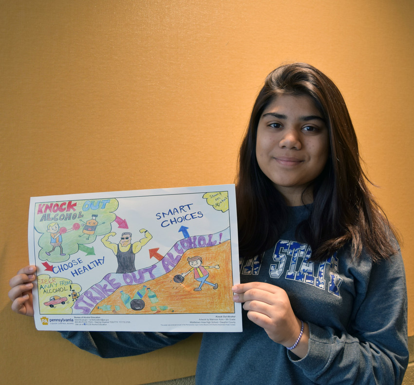 Mahnoor Azim holds her poster honored in a statewide contest.