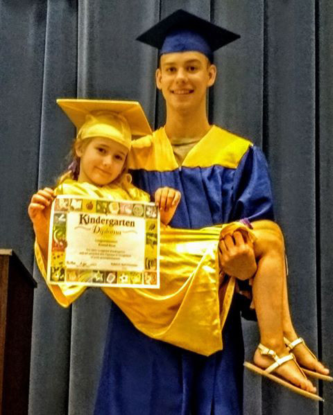 Middletown Area High School 2018 graduate Grayson Meyer holds his little sister Kennedi; who graduated from kindergarten at Reid Elementary School on the same day.